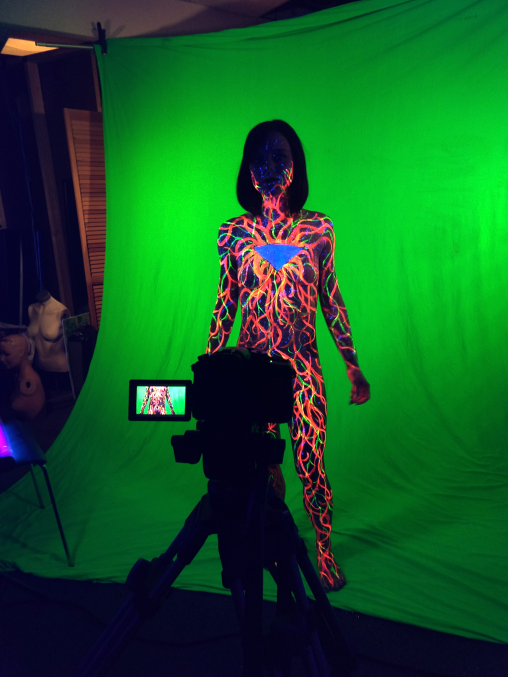 Image still from video. A painted human body in front of a green screen.